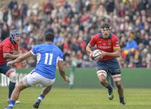 un joueur de Rugby cours ballon en main